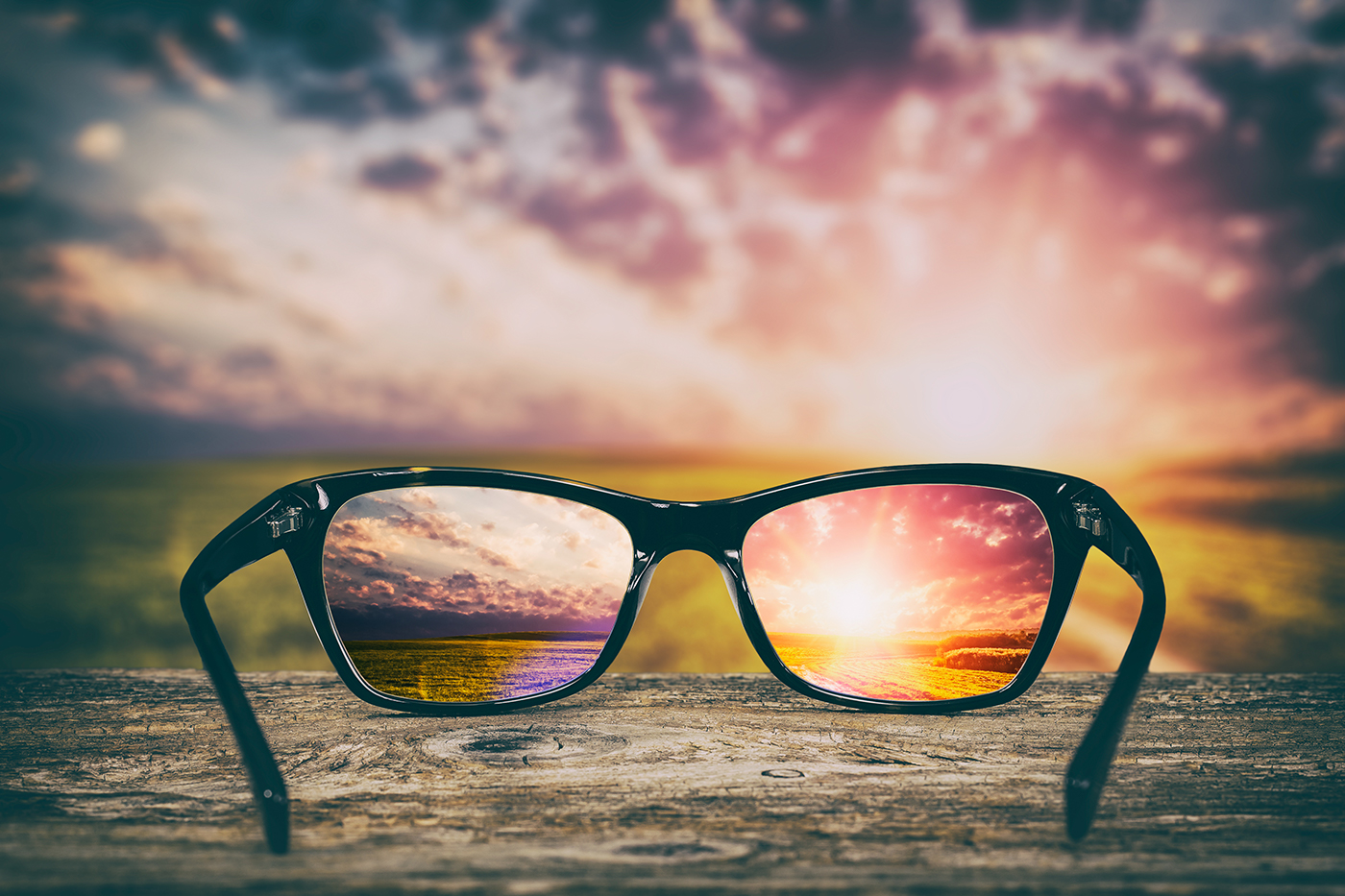 An out-of-focus view of a sunrise, with a focused version in the lenses of a pair of spectacles.